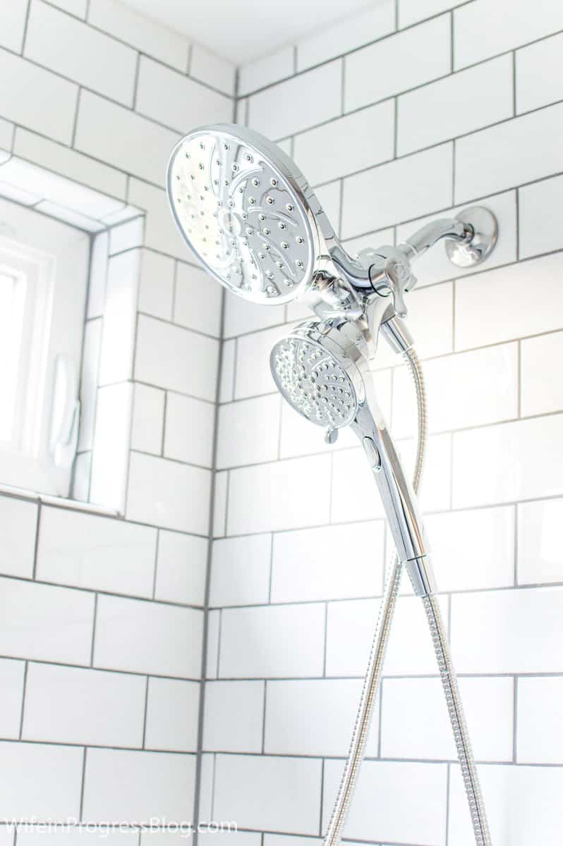 Chrome shower accessories and white subway tile with medium gray grout