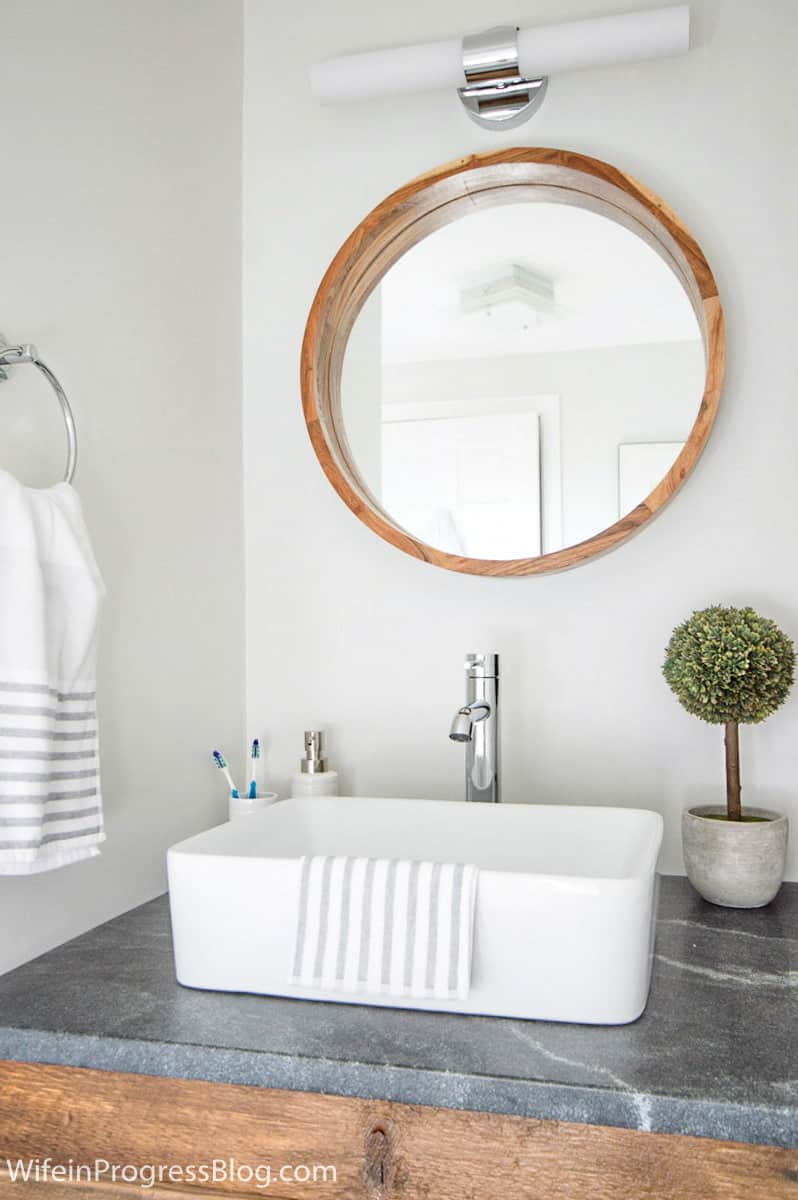 Large round wood-framed mirror complements straight lines of light fixture, vessel sink and wood vanity