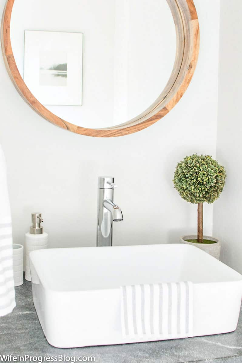 White vessel sink and chrome faucet, installed on granite & reclaimed wood vanity