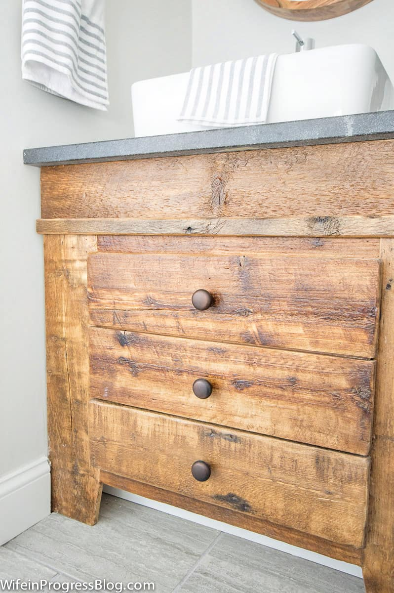 Closer look at wood details of reclaimed wood vanity that add charm to a farmhouse bathroom