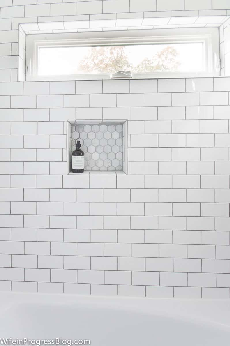 Medium gray grout white subway tile. Hexagon marble tile in shampoo niche. Oblong horizontal window in top frame.
