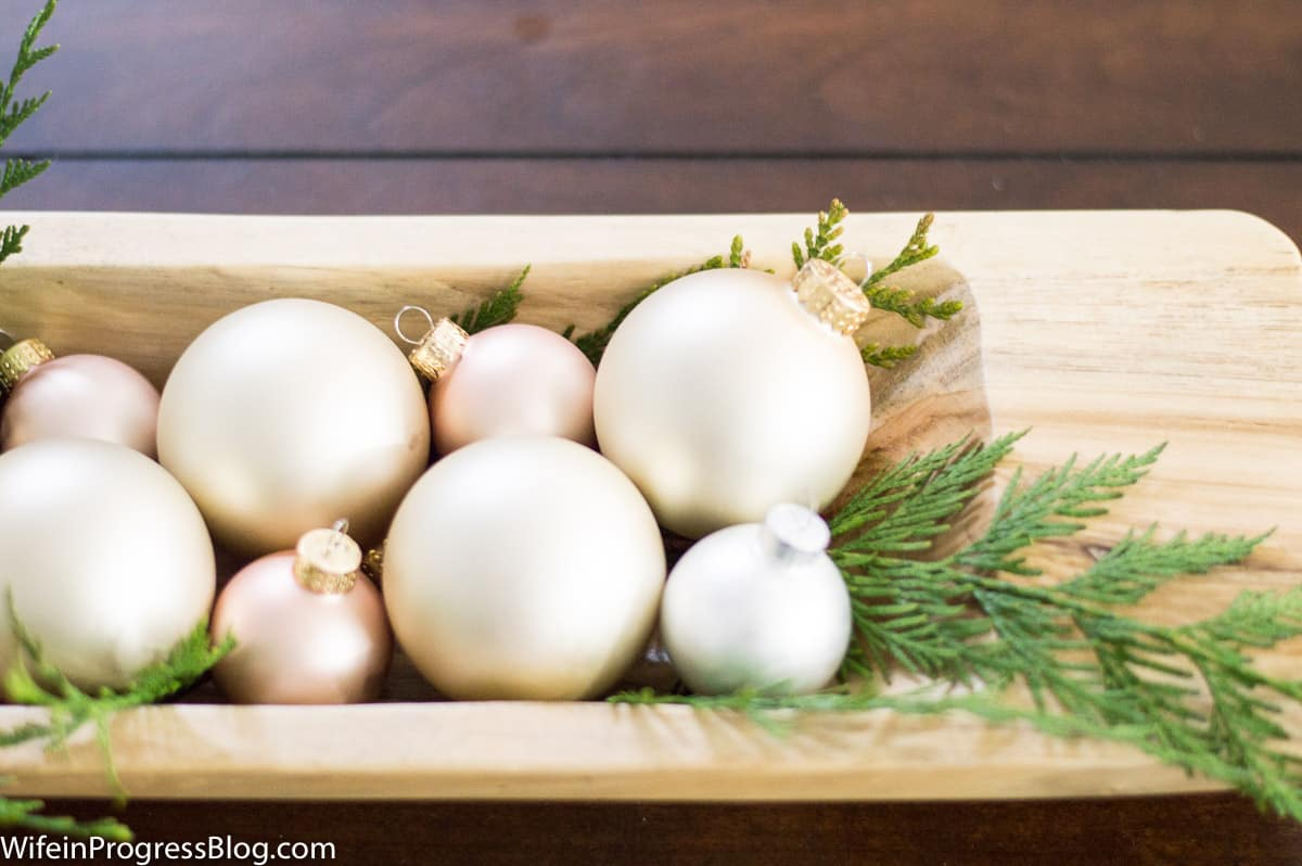 Add some fresh greenery to a dough bowl with ornaments. Farmhouse style Christmas decorating ideas that are easy to copy in your own home!