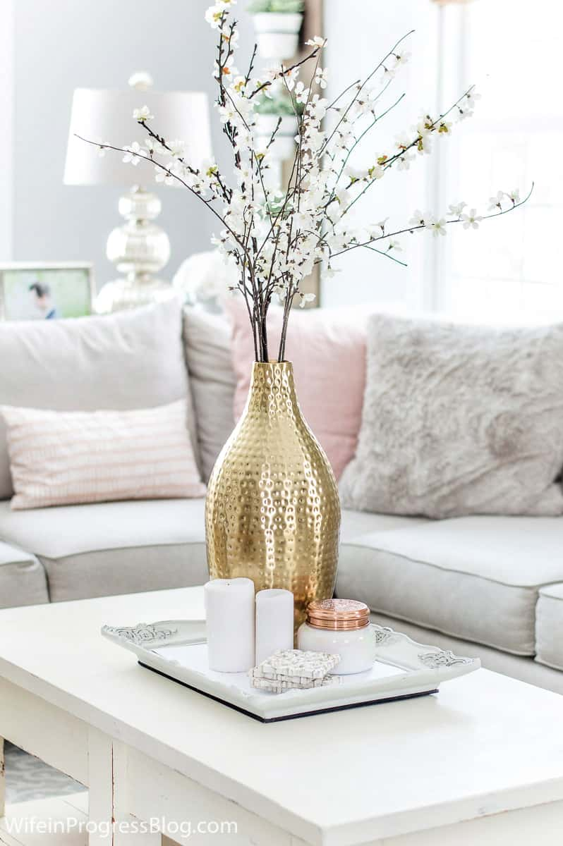 Blush pink and faux fur are trendy winter decor this year. They create a soft and romantic feeling in this living room. Get more tips for winter decorating by clicking through!