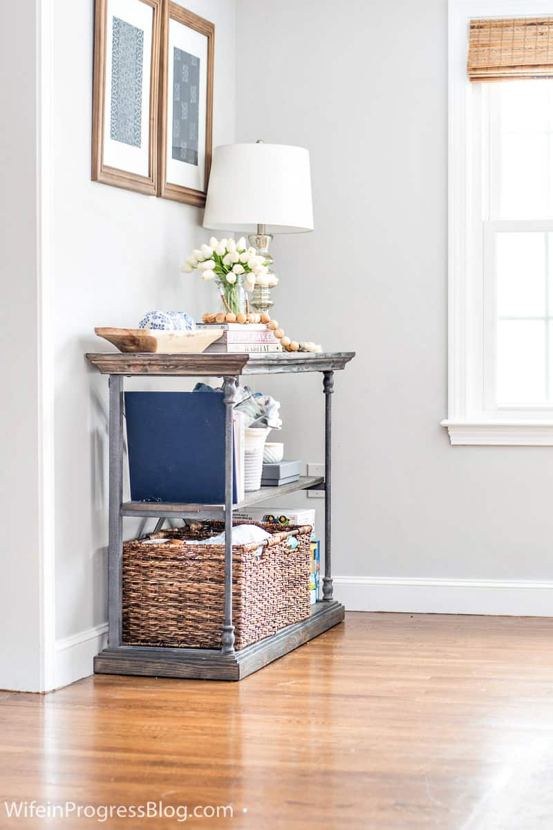 Simple way to hide to clutter in a living room. Use baskets in a console table like this
