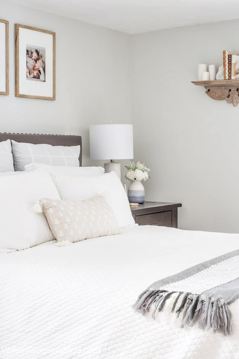 A cohesive color palette of grays, whites and taupes pulls this small master bedroom together and makes it feel bigger than it is.