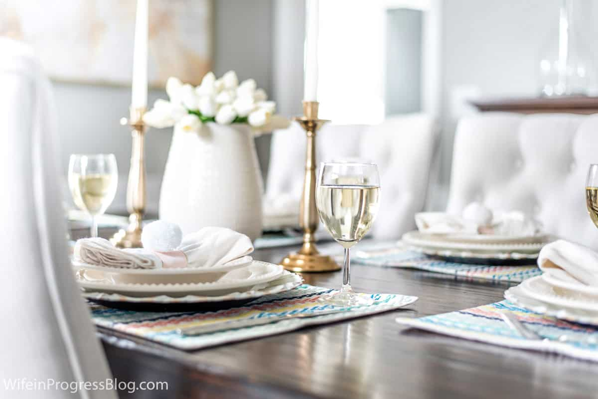 An Easter table setting with white tulips, colorful placemats and easy DIY napkin rings