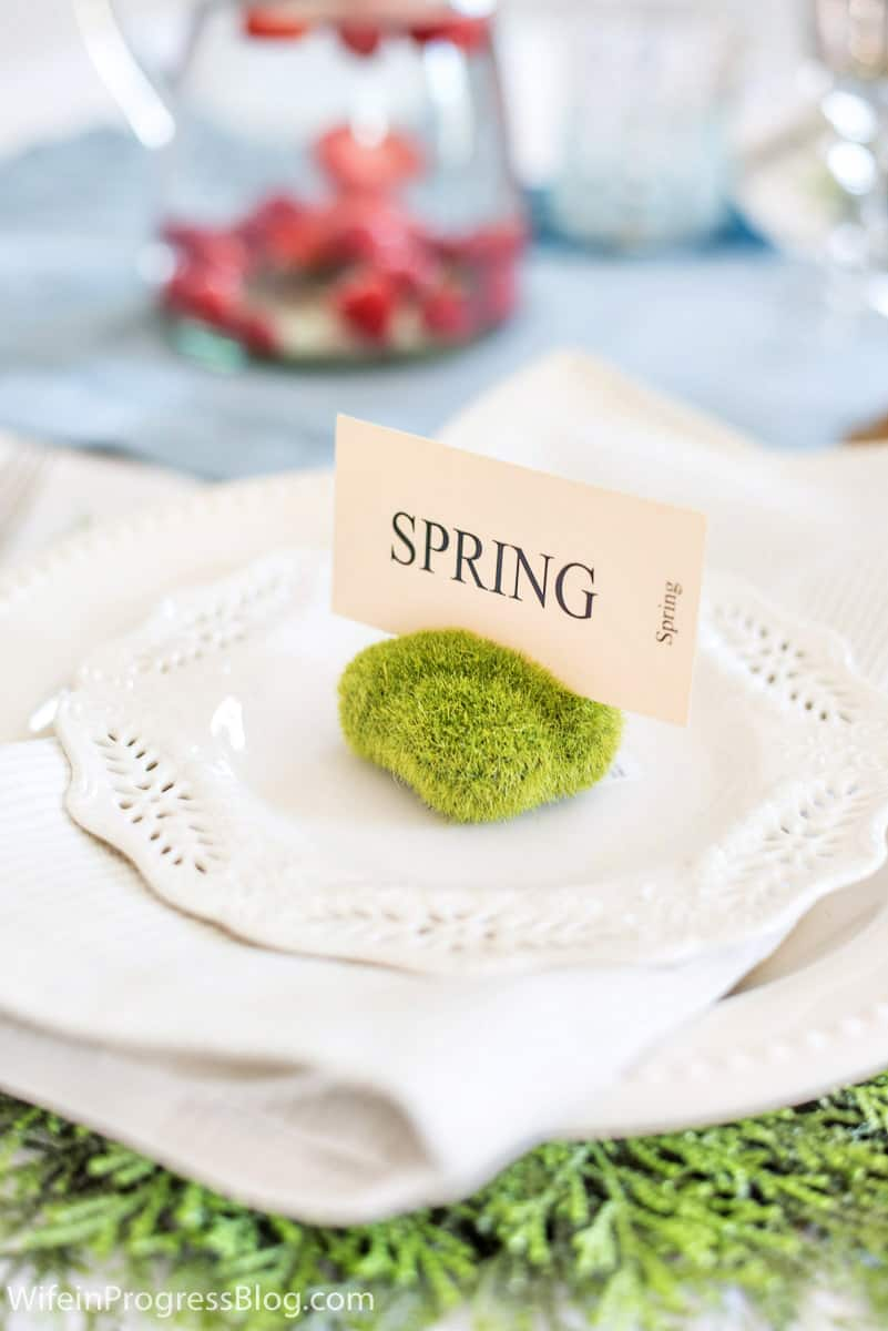 Close-up of a Spring table setting with a mossy rock and place card