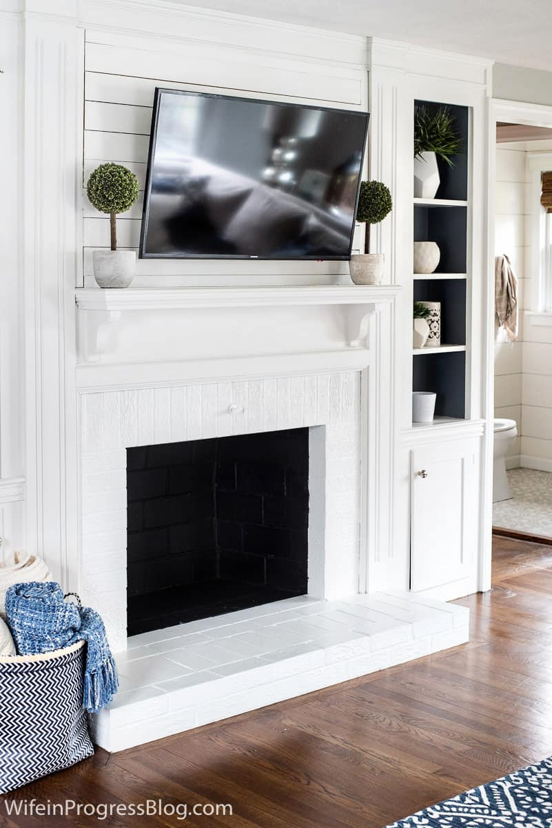 White fireplace, with white mantel and television overhead, topiary plants on either side of mantel