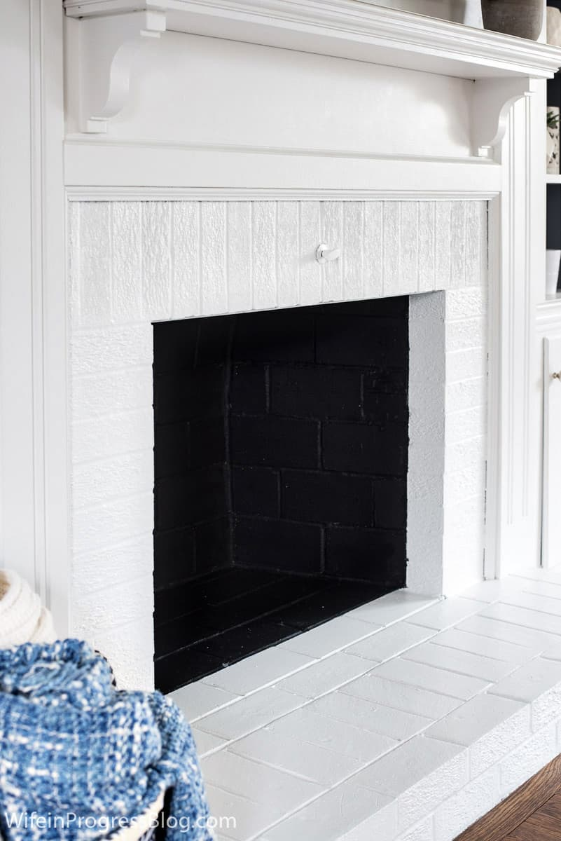Interior of fireplace painted black set against crisp white fireplace.