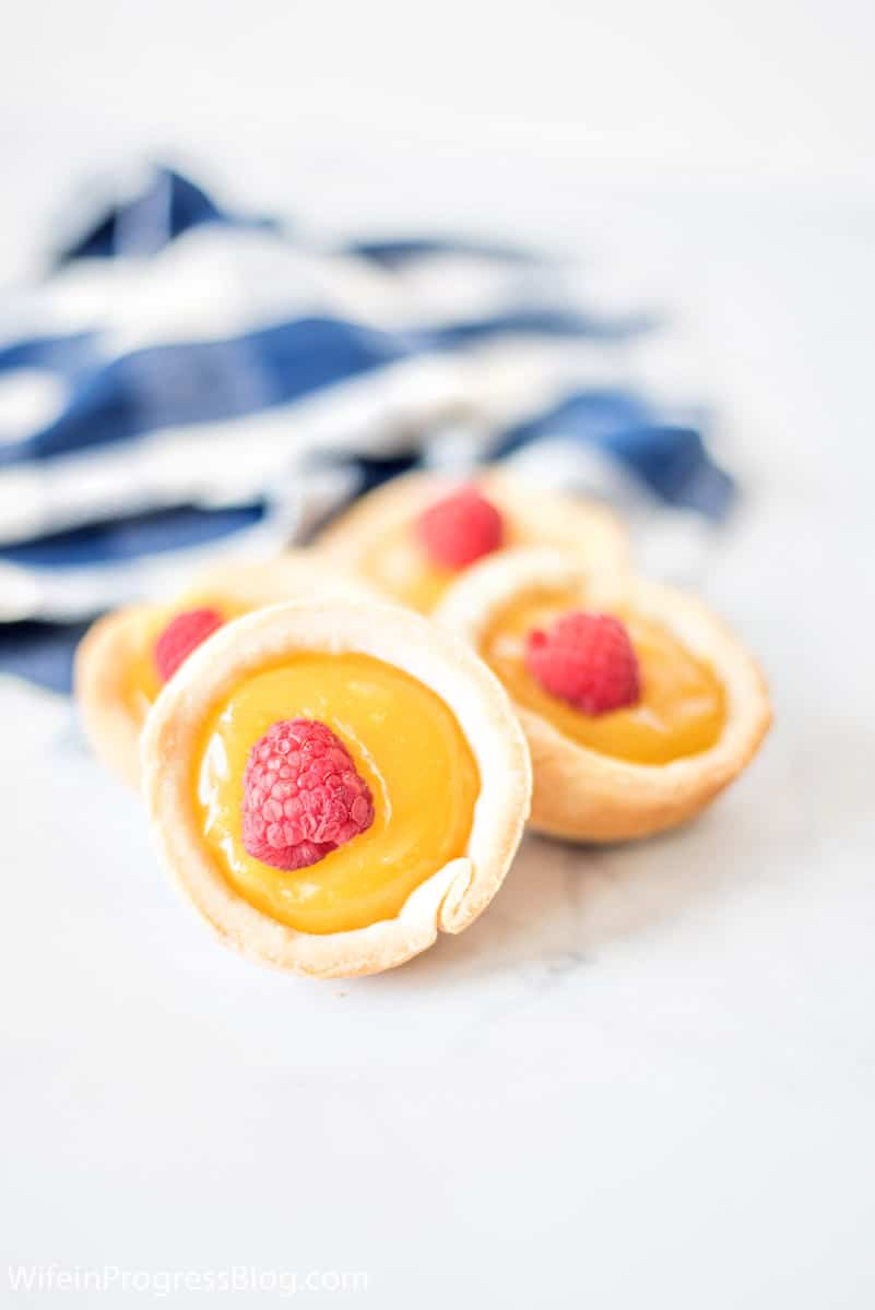 mini pie shells filled with homemade lemon curd and topped with a raspberry