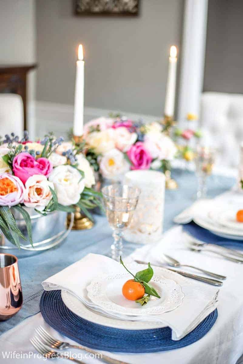 Simple and elegant Mother's Day tablesetting with bright peonies and mandarin oranges on each plate