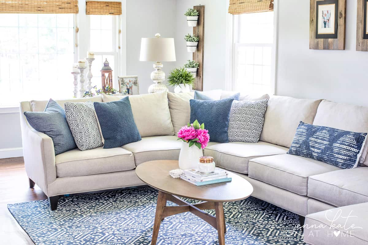 neutral couch with navy blue throw pillows and navy and white living room rug