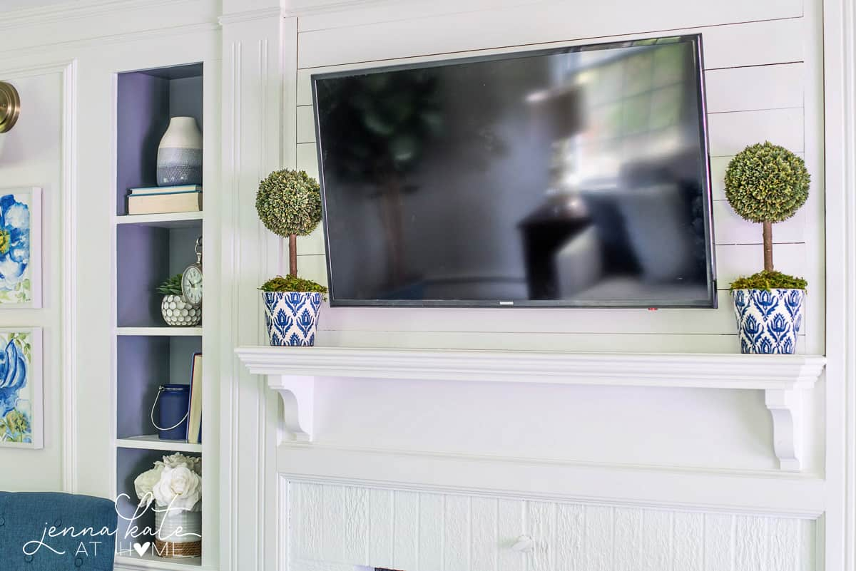 A white painted fireplace is the focal point of this navy blue coastal living room
