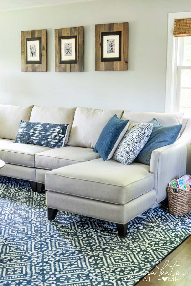 Blue rug under a large beige sectional.
