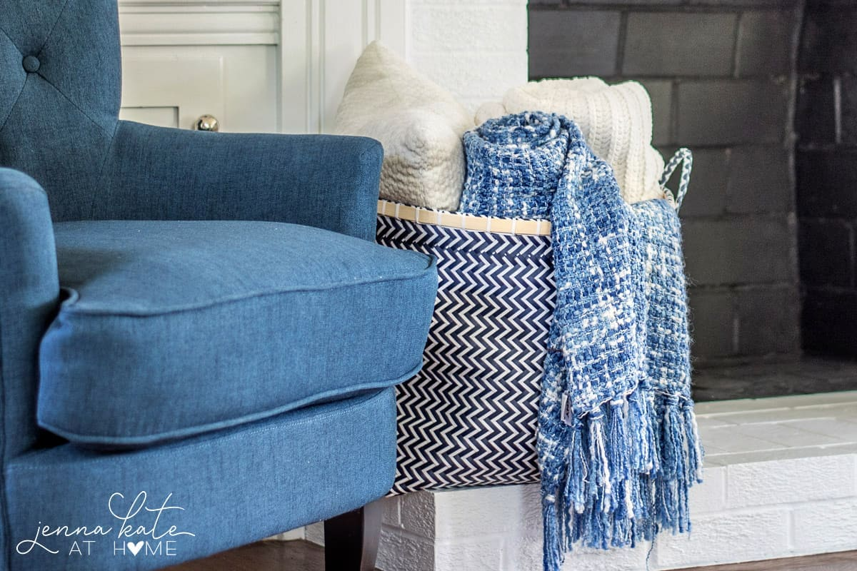 Cozy throws add warmth and texture to this navy blue coastal inspired living room
