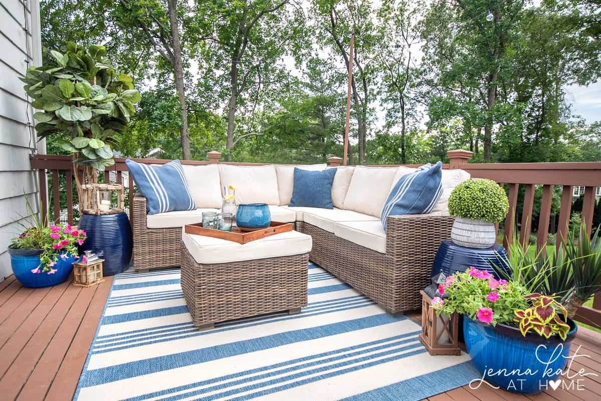 small deck decorated for summer with a sectional, rug and plants