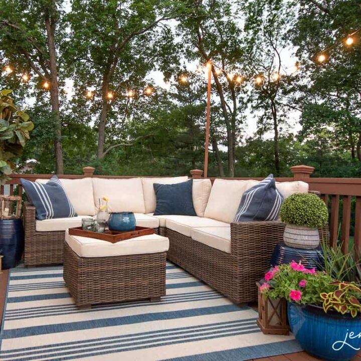 An outdoor wooden deck with blue and white furniture & decor, under a canopy of string lights