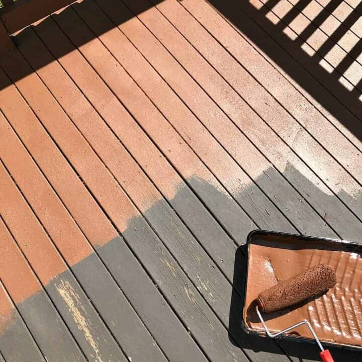 Old brown deck surface in the process of being coated with a resurfacing product using a paint roller