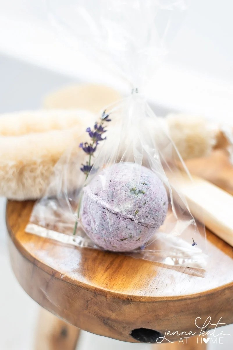 Purple bath bomb wrapped in cellophane bag with sprig of lavender, next to bath accessories