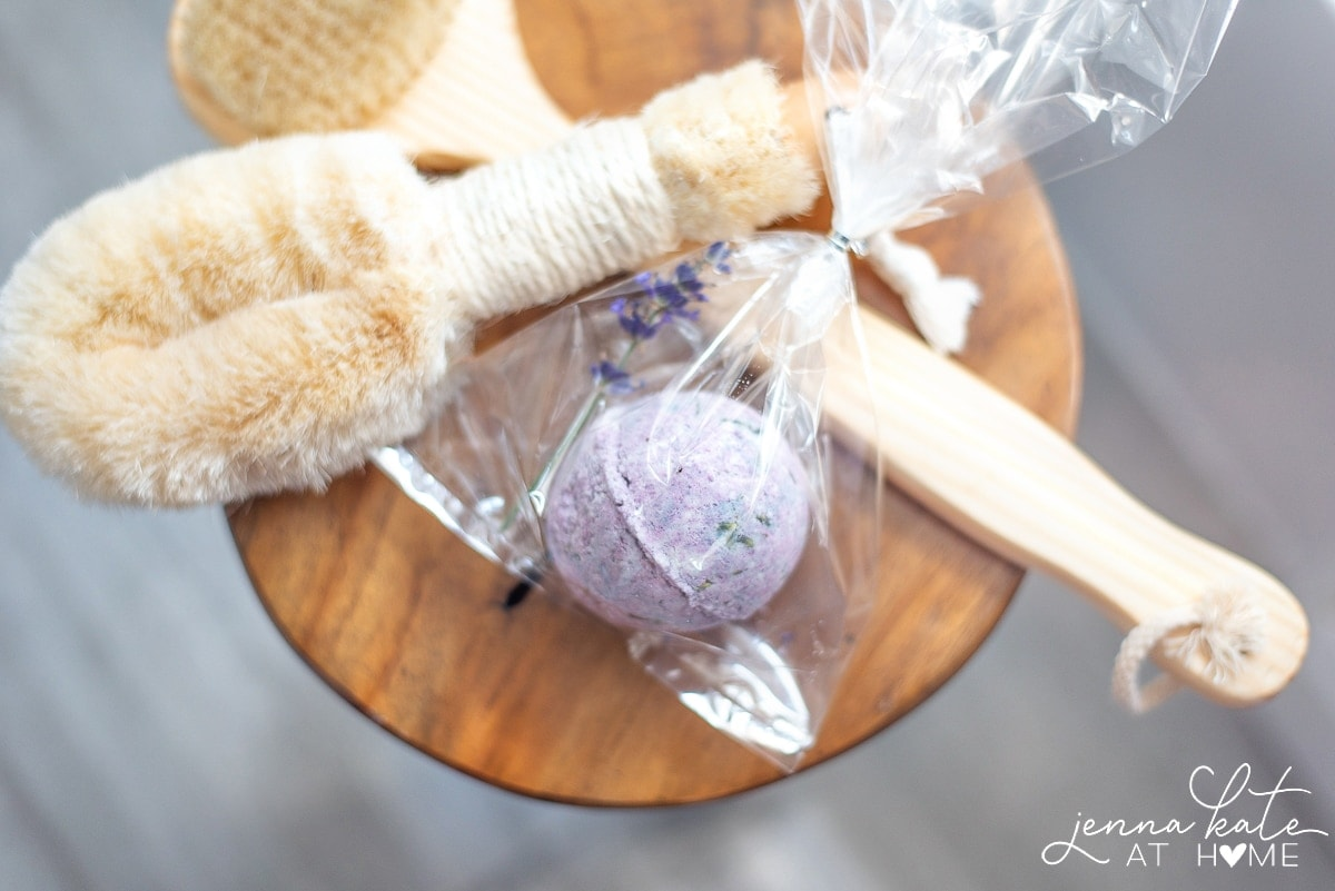 Bath bomb and various bath brushes on wooden stool