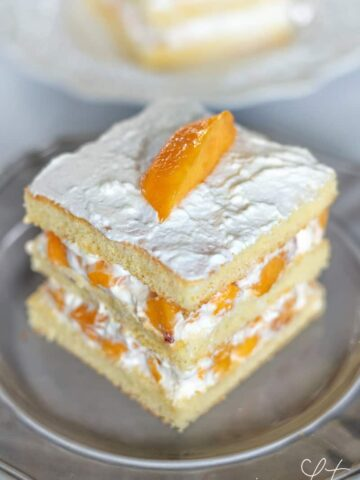 An easy sponge cake layered with fresh peaches and homemade whipped cream.