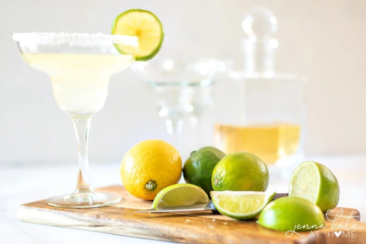 Cutting board with limes, lemons and a glass of homemade margarita mix