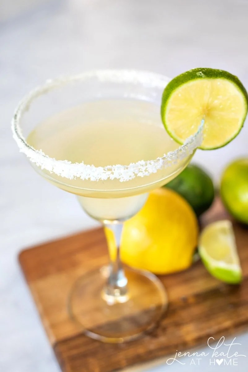 close up of a salt rimmed margarita glass garnished with a lime