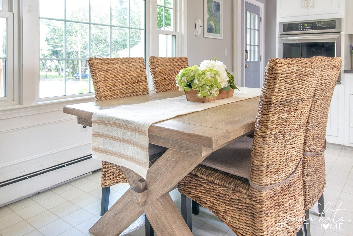 A wooden dining table in the kitchen with  4 wicker chairs, a burlap table runner extending over the sides, and a tray of assorted greenery as a centerpiece.