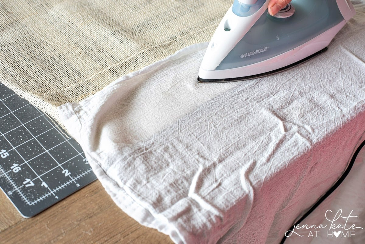 An iron is run over the burlap hem with a tea towel as a buffer, to secure the hem to the fusing tape.