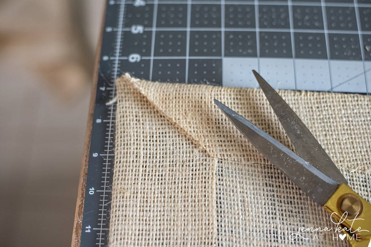 A fabric scissors is used to cut edges on a diagonal for clean corners on your diy table runner