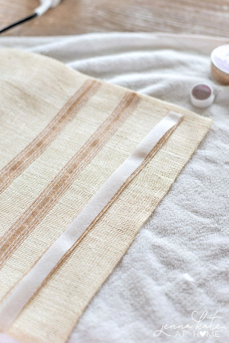Burlap ribbon with white stitching is added with fusing tape to the edge of the short side of the burlap table runner