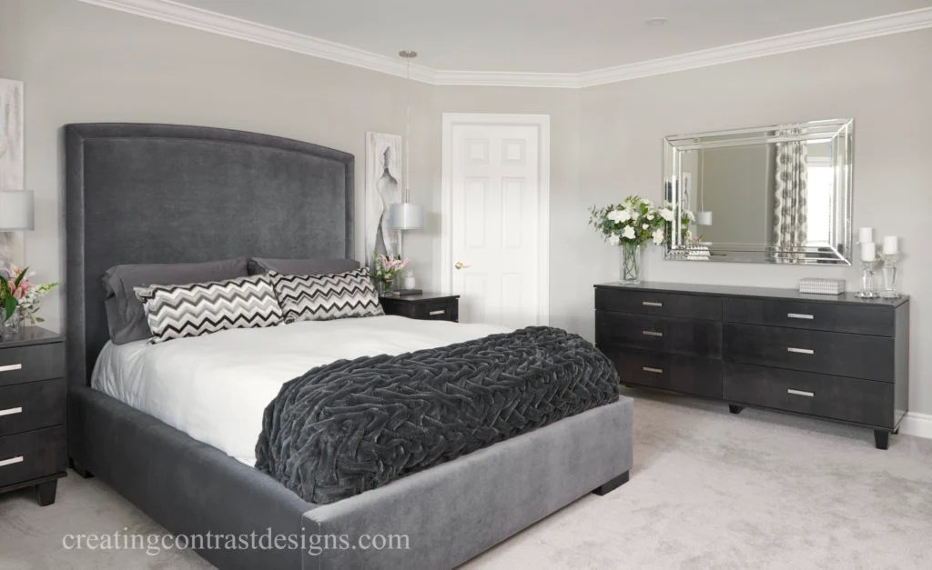Bedroom walls painted revere pewter with black furniture and dark gray bed.