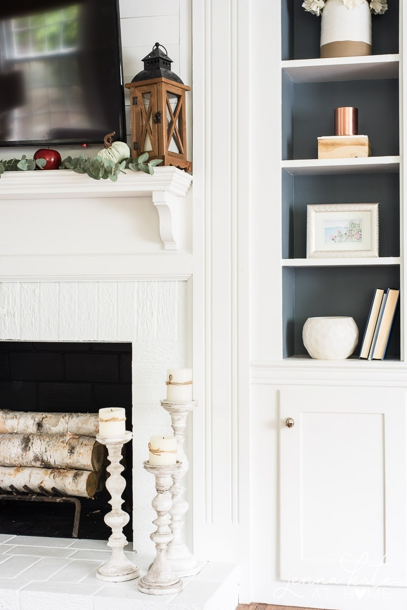 I added pops of green, red, and dark wood to my all-white fireplace mantel for some affordable fall mantel decor