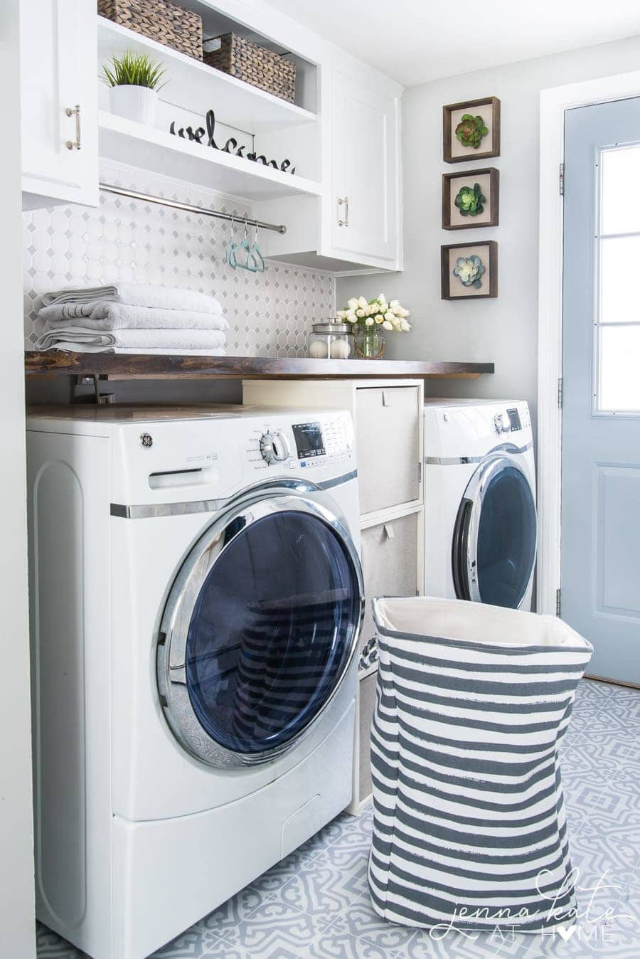 A view of the finished laundry room where the countertop now holds towels, a vase and a jar of dryer balls.