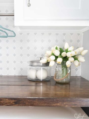Bouquet of white flowers and glass jar rest on wooden countertop in laundry room