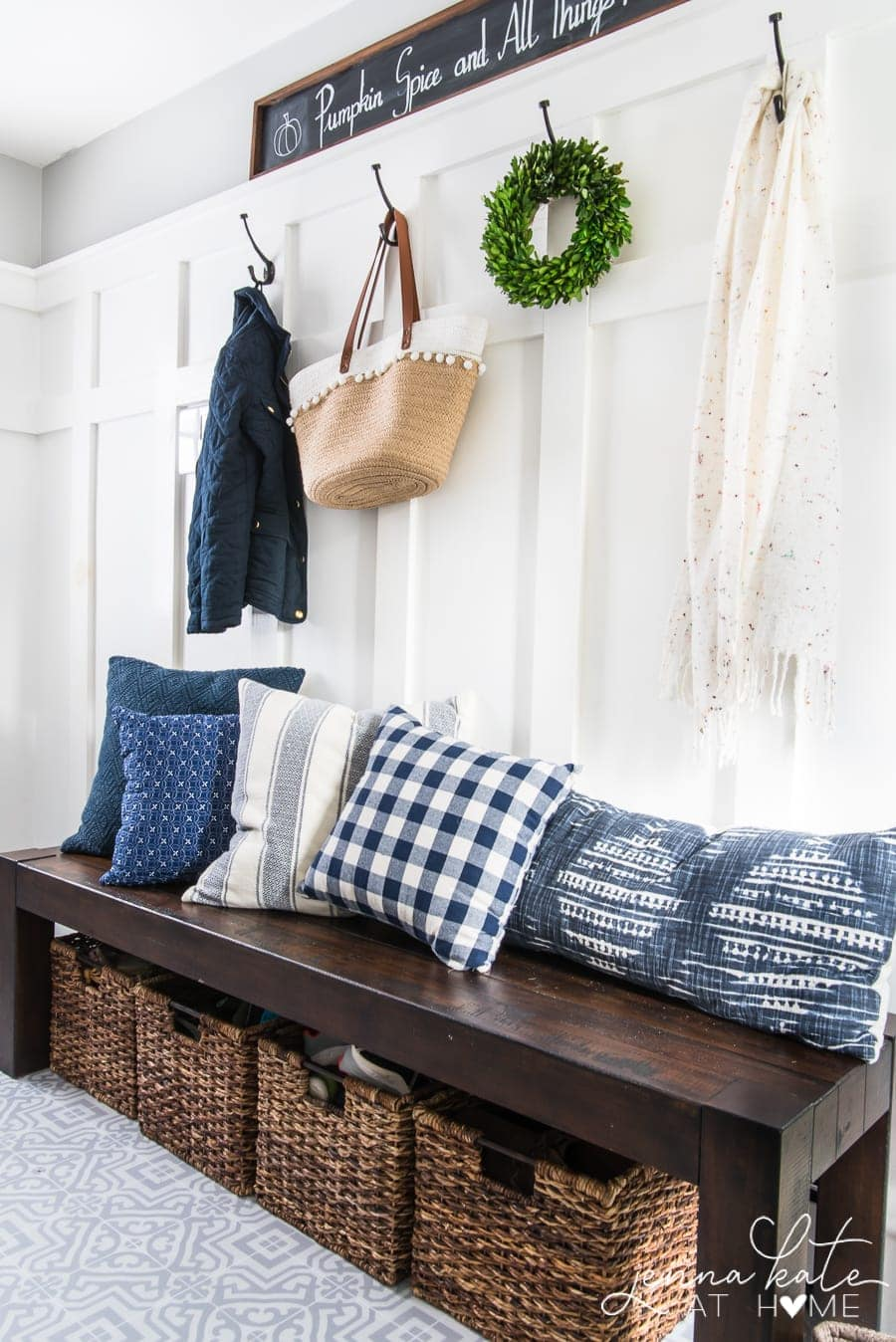 Organized mudroom with items on hooks and shoes in a basket under a bench