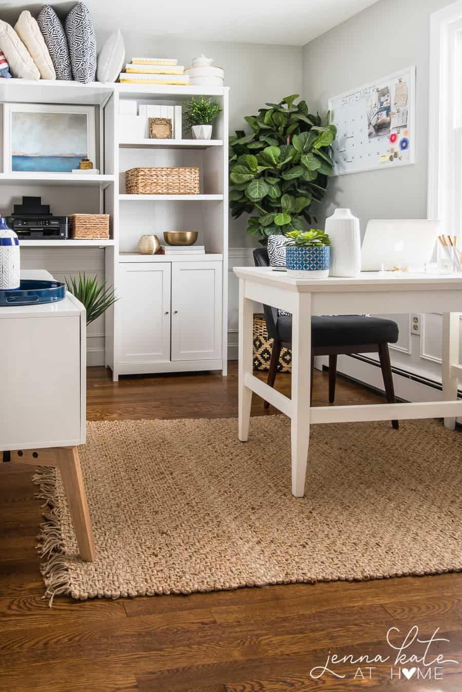 office with dark wood floors, jute rug and white furniture