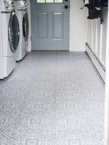 Gre and white patterned vinyl decal sticker sheets applied to floor of laundry room,