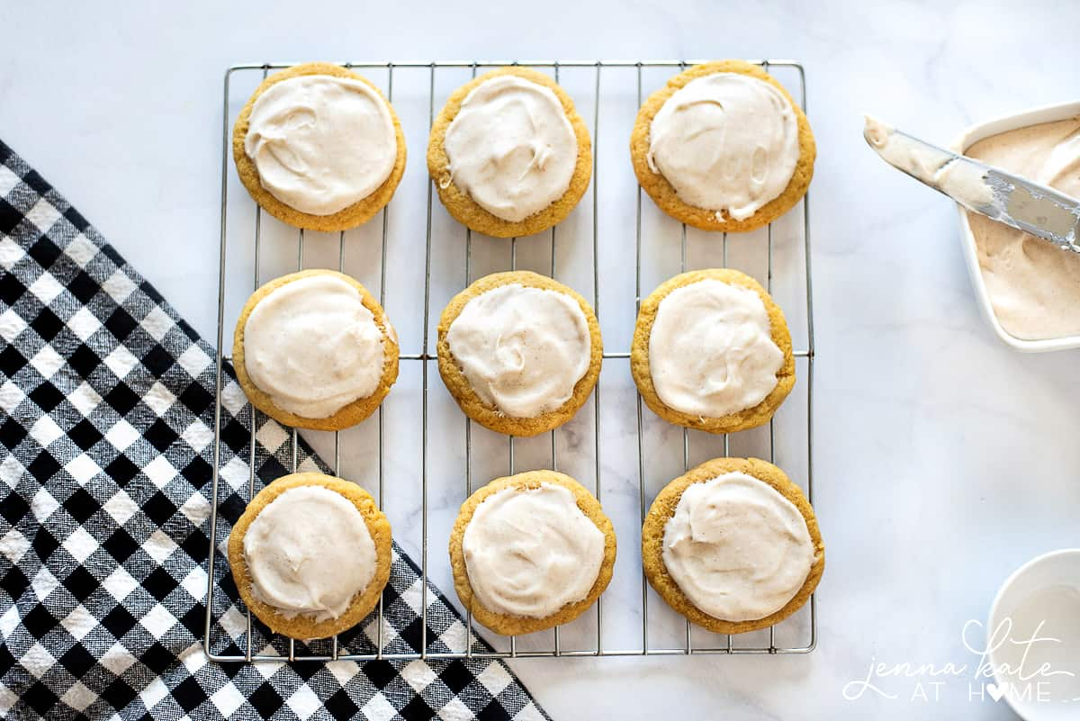 Pumpkin sugar cookies with cinnamon cream cheese frosting, resting on wire cooling rack