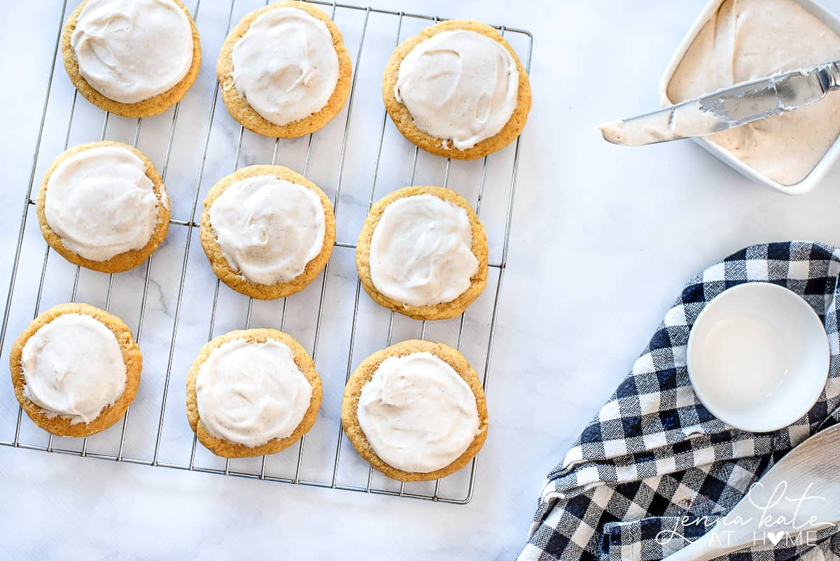 Pumpkin sugar cookies resting on cooling rack, with a bowl of cream cheese frosting and spreading knife nearby