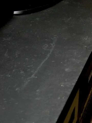 Distressed countertops painted with black chalkboard paint and sealed for a stone look