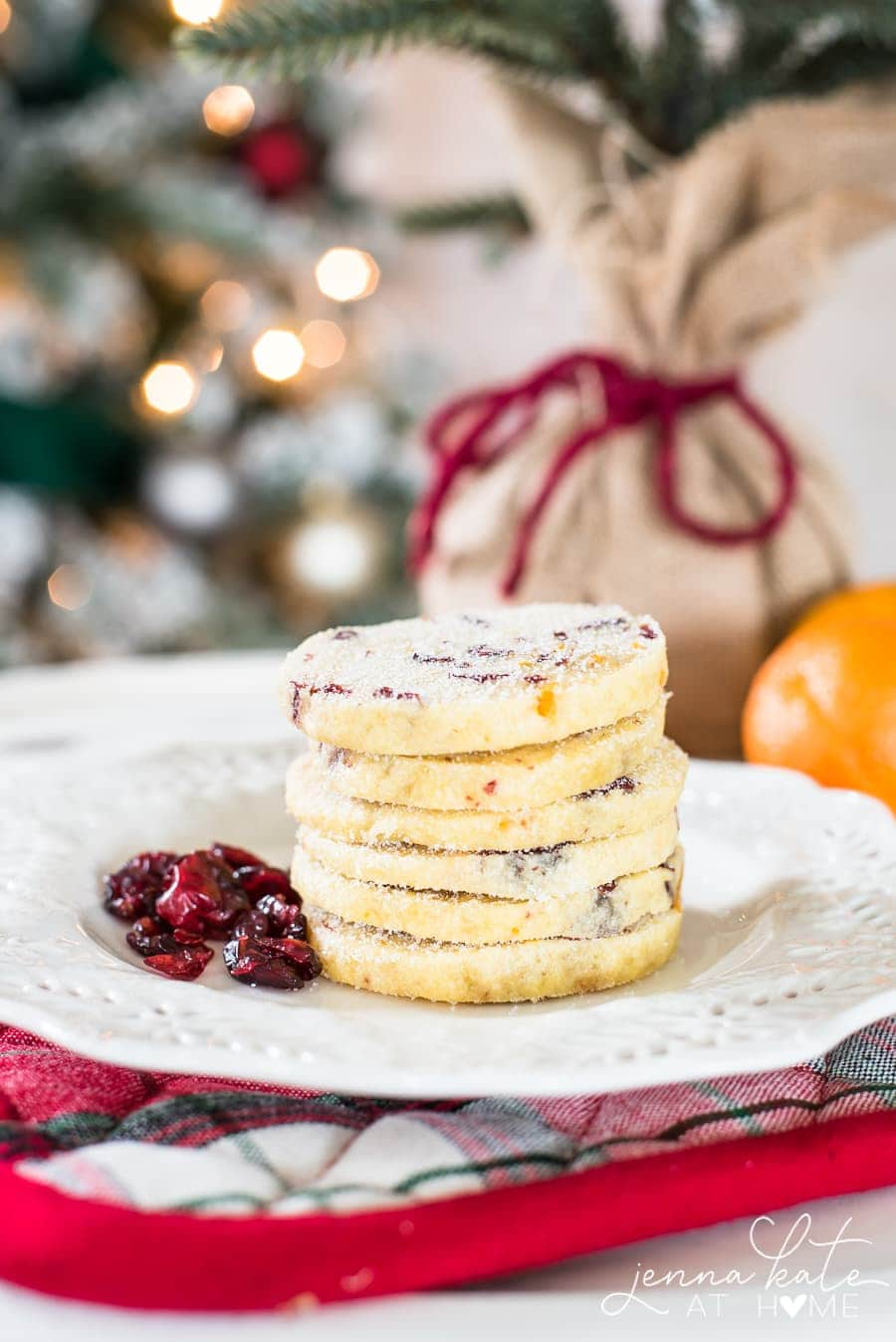 Christmas shortbread cookies stacked high with dried cranberries on a plate