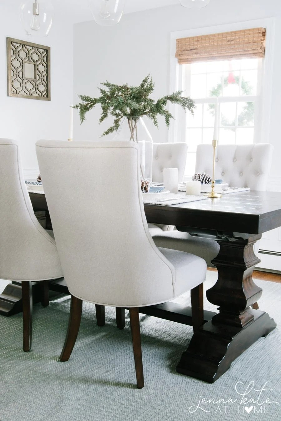 Light gray dining room with a dark wood table with a winter themed table setting