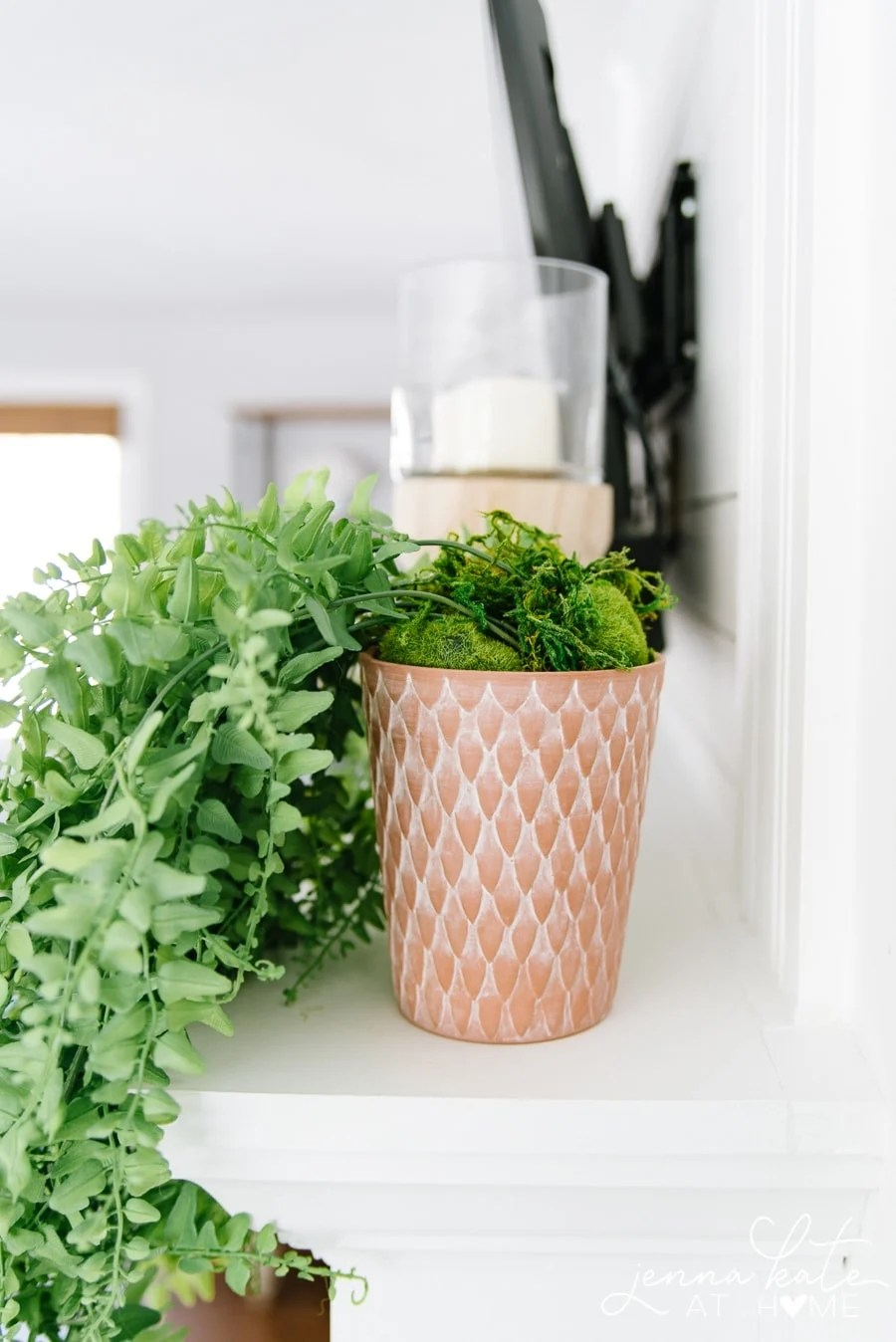 Faux moss and rocks help conceal the stems of your potted faux trailing plant