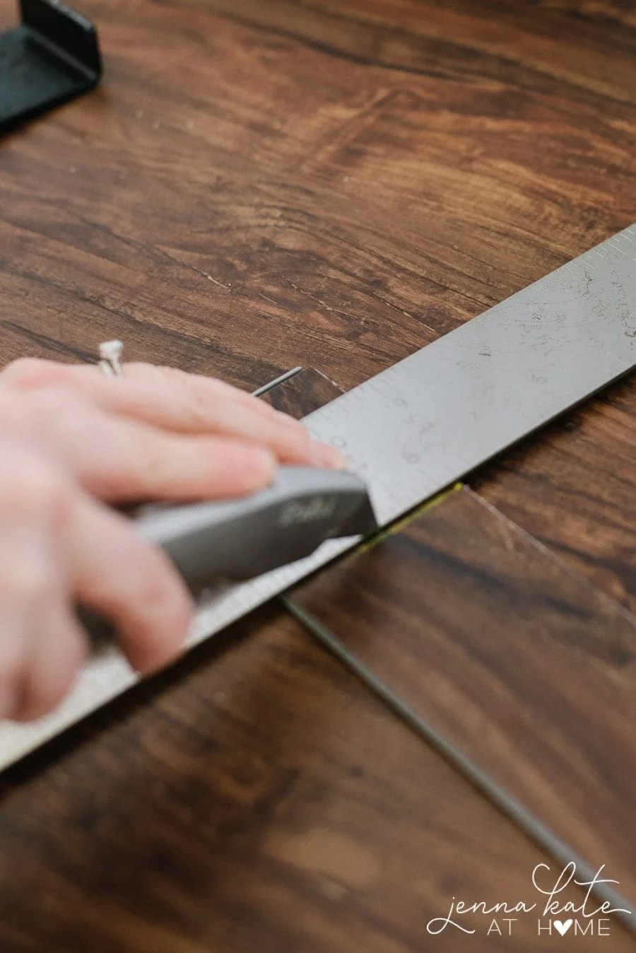 Using a box cutter to cut vinyl planks