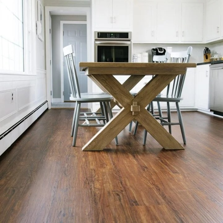 A wooden dining table and chairs resting on newly-installed wide, brown luxury vinyl planks