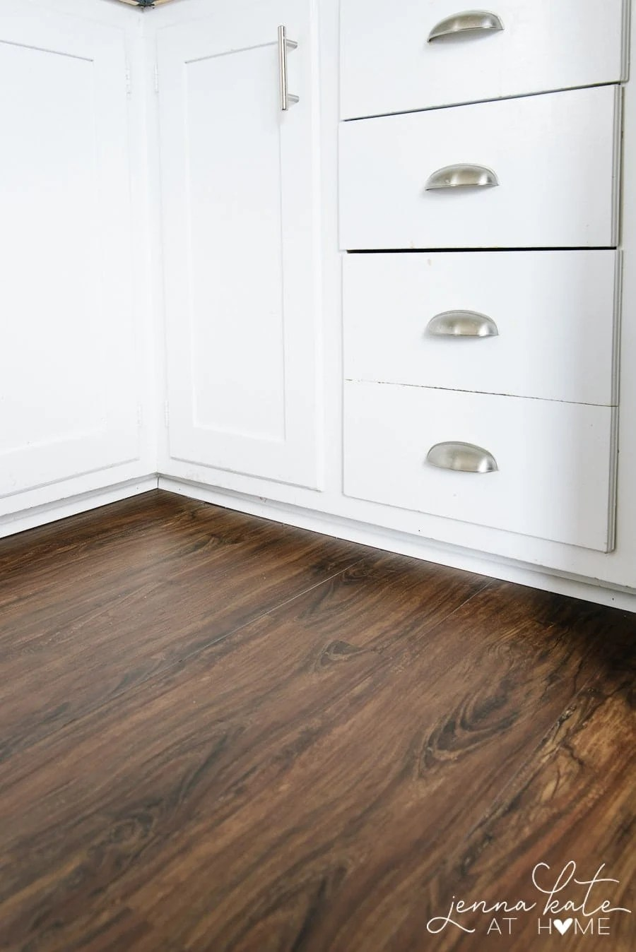 The edges of the luxury vinyl plank up against kitchen cabinets and secured with shoe molding