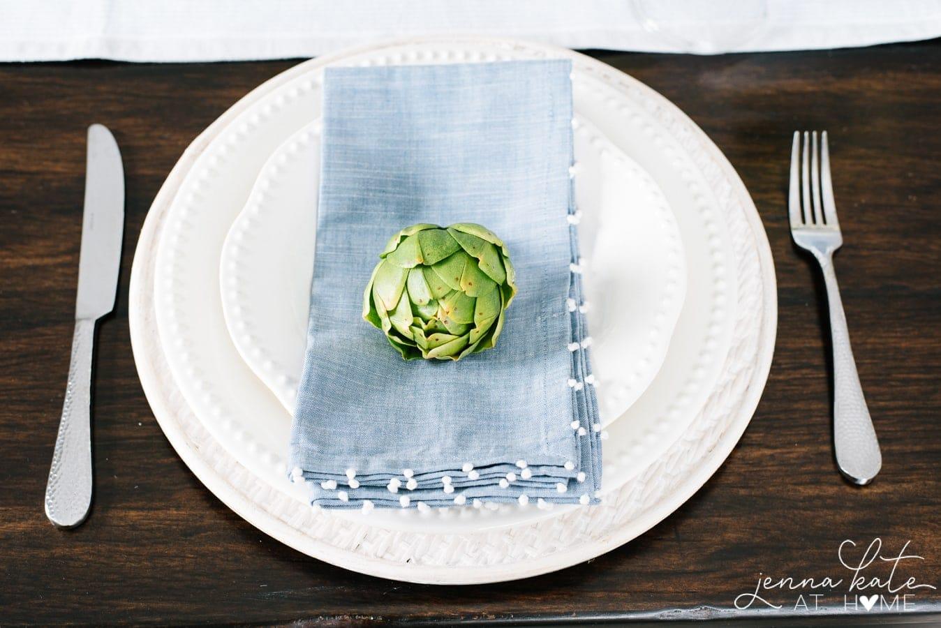 white dinnerware with blue napkin and faux artichoke