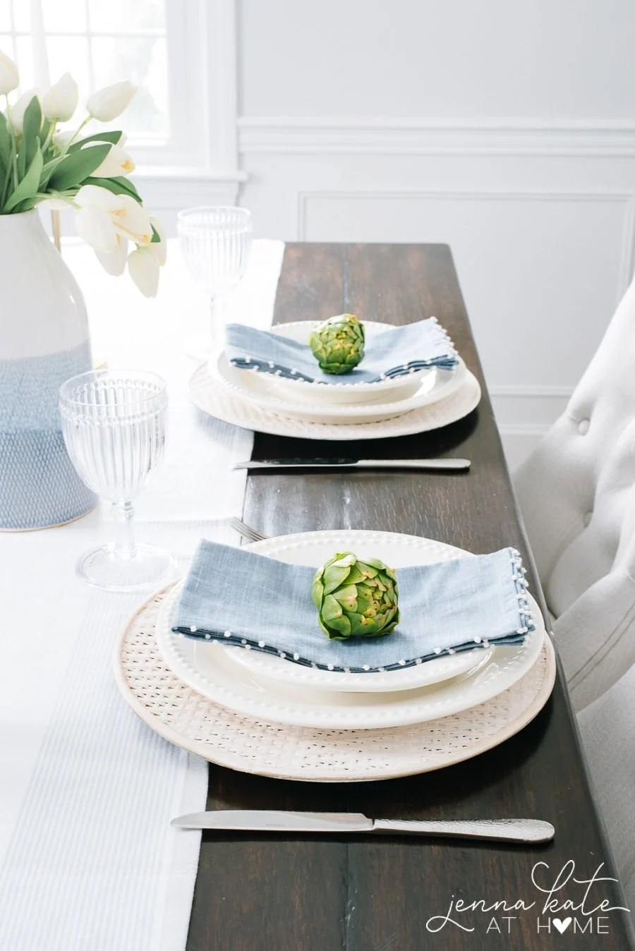 close-up of spring place settings with blue linen napkins and artichokes