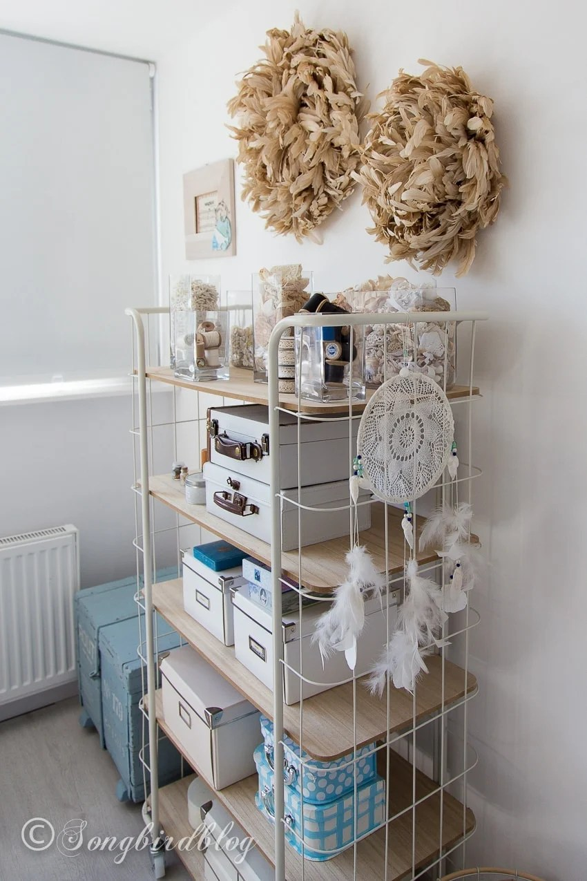 Use a rolling cart and decorative vases to store small items when organizing your craft room